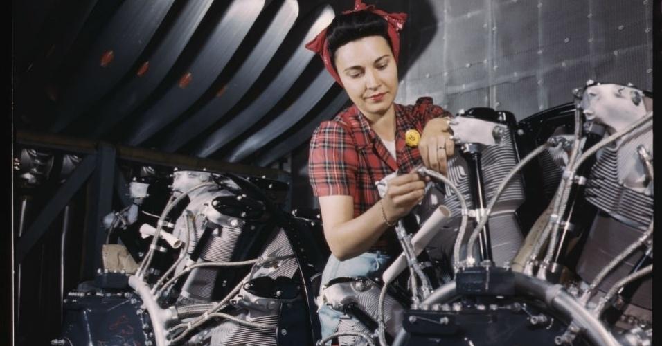 """Trabalhadora na fábrica de motores da North American Aviation, Inc., Inglewood, Califórnia. Foto de Alfred T. Palmer, de 1942. Durante a Segunda Guerra Mundial, as mulheres ocupavam as linhas de produção da indústria de aviões, motores, munição e trens. A exposição inédita """"Operárias da Guerra - Razões e encenações"""" traz imagens deste período, datadas de 1942 a 1945. As imagens integram o acervo americano do Office of War Information e eram usadas como propaganda política do governo para chamar mais mulheres para o trabalho. A exposição fica em cartaz de 4 de março a 12 de maio, de segunda à sexta, das 10h às 18h, na Madalena Centro de Estudos da Imagem (Rua Faisão, 75, Vila Madalena), com entrada gratuita. Mais informações no telefone (11) 3473-5412 ou no site madalenacei.com.br."""